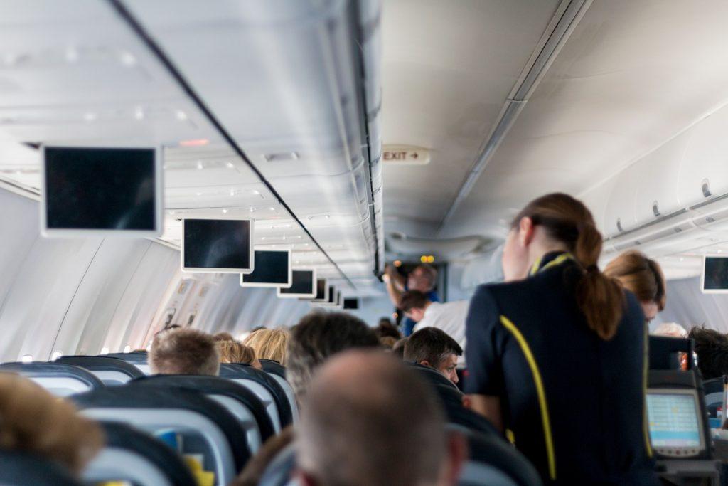 Auf dem Bild ist das Innere eines Flugzeugs mit Passagieren und Flugbegleiter*innen zu sehen.