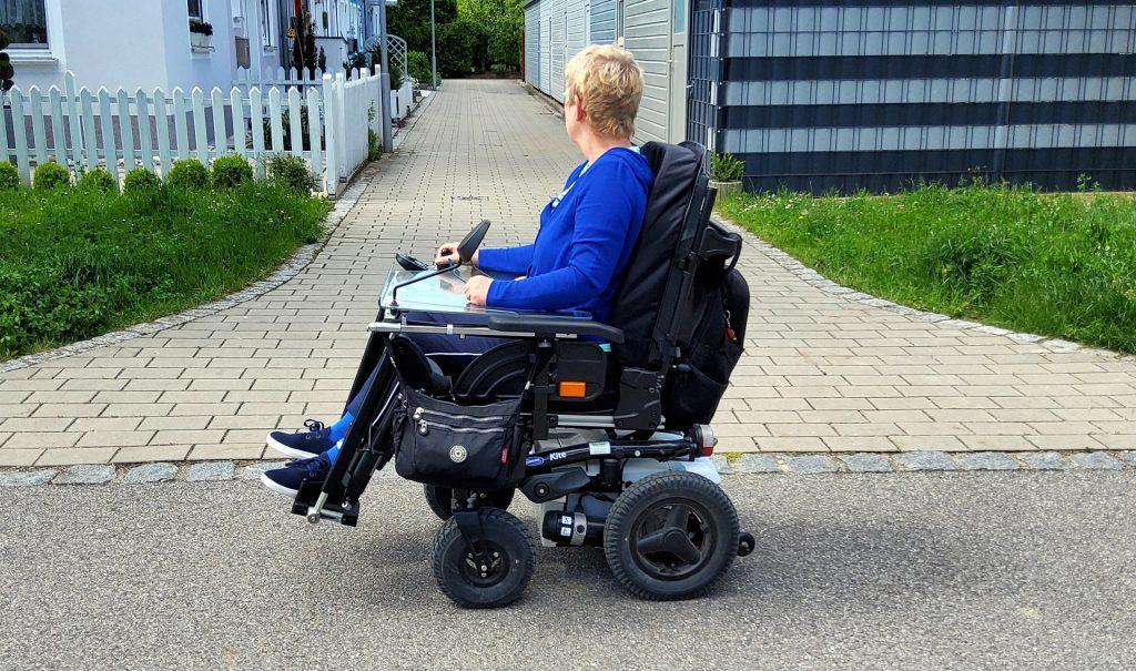 Rollstuhlfahrerin vor Eingang zu einer Wohnhausanlage, der gepflastert ist.
