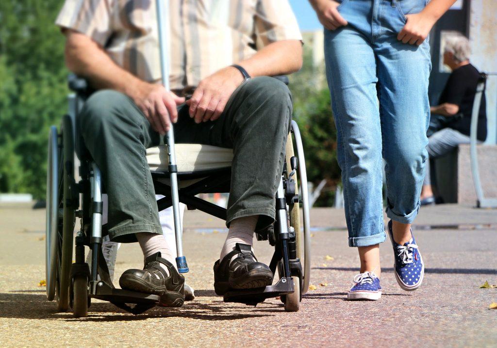 Älterer Rollstuhlfahrer und junge Frau nebeneinander.