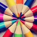 Auff dem Bild liegen Buntstifte in verschiedenen Farben im Kreis, Spitze in die Mitte.
